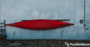 Storing a kayak outside - Red kayak hanging on a wall
