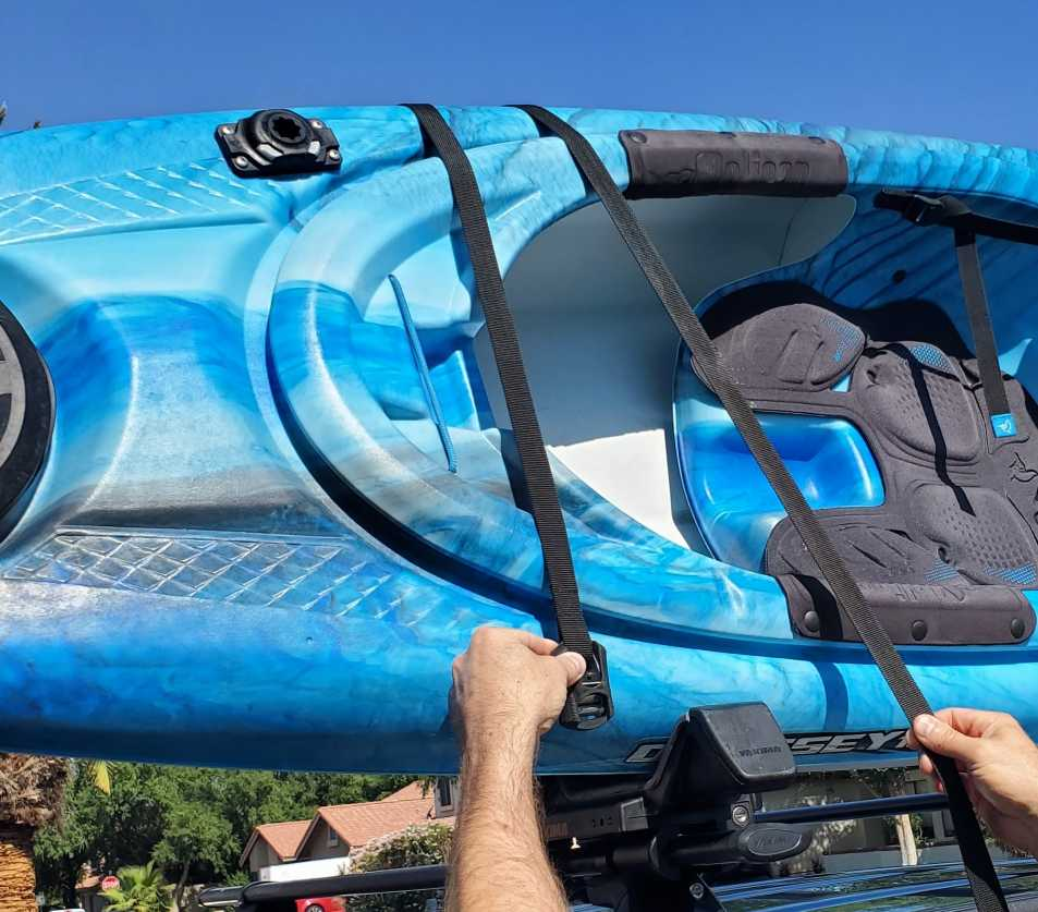 Loading a kayak on a j cradle - straps are positioned on either side of the crossbars