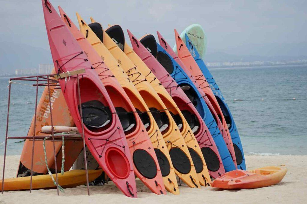 The best kayak brands - Kayaks standing up in a rack on the beach
