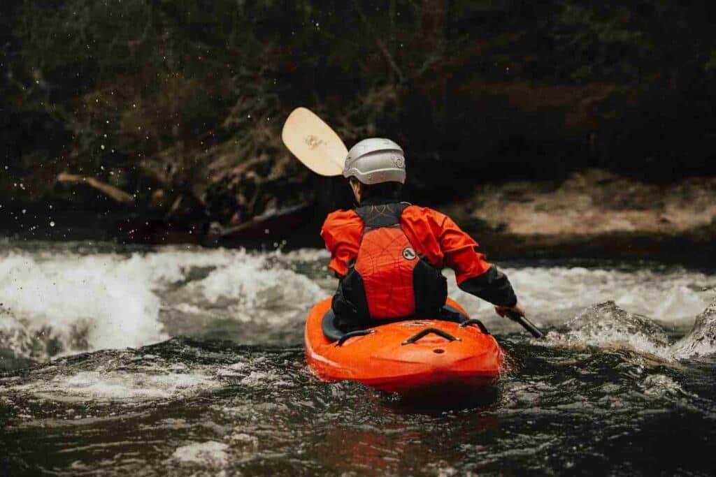 Man going through whitewater in a kayak