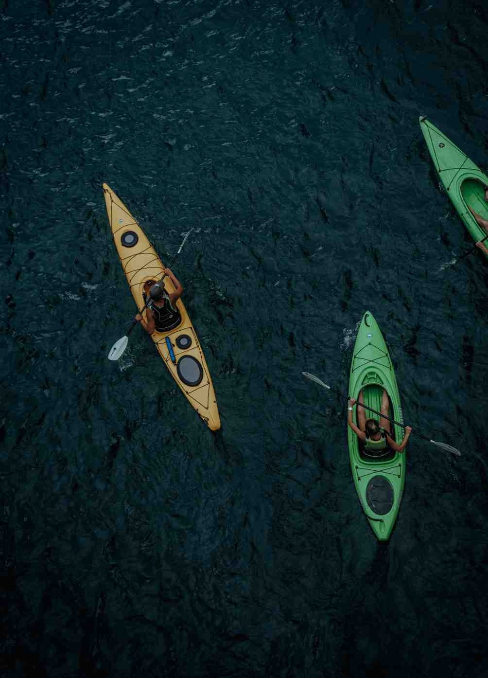 Three people in different types of kayaks